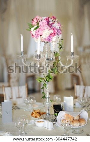Antique candlestick with wedding bouquet.wedding candlestick with flower decoration before wedding ceremony.Tables set for a wedding reception