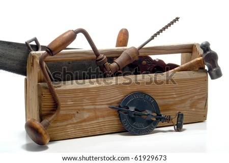 Antique carpentry and construction work tools collection with spindle tool in an old vintage wood toolbox over white