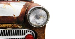 Antique cars with rust. Detail of the front headlight of an old car isolated on white background.  front of a rusty old and retro looking light car on white.