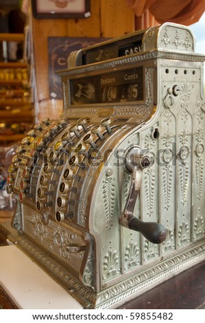 antique cash register in a setting suggestive of an old general store; selective focus