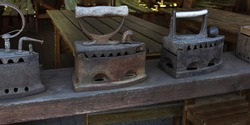 antique charcoal irons. Vintage irons in row on wooden shelf.Old fashioned ironing tools.Heritage concept