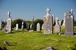Antique Christian graveyard with old tomb stones at daytime, in Ireland