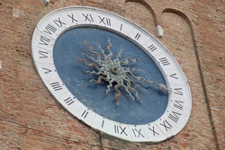 antique church clock on brick wall of church tower sun and sun rays as clock hands on blue clock face, black Roman numerals on white ring