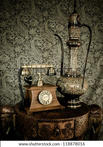 Antique classic furniture with old retro phone and indian arabic tea pot on a retro elephant styled desk