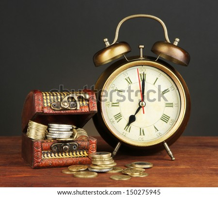 Antique clock and coins on wooden table on black background