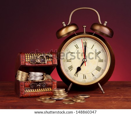 Antique clock and coins on wooden table on dark color background