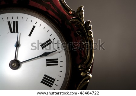 Antique clock face with hands over roman numerals marking time