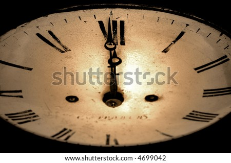 Antique clock face with the hands at 12 o\'clock, sepia toned image.