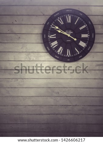 Antique clock on the wall show ten minutes to ten o'clock, dark vintage picture