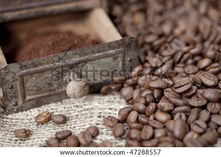 Antique coffee grinder filled with coffee beans and ground coffee - selective focus