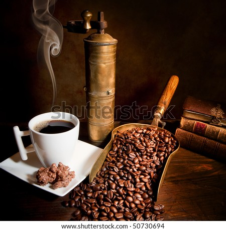 Antique coffee grinder with steaming coffee, cookies and books