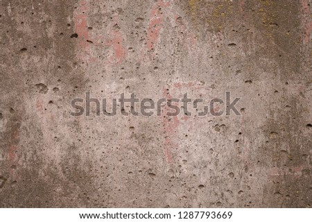 Antique concrete surface with grooves. the background is a gray wall texture with a slight pink tinge; on its surface there are a lot of holes, recesses, scuffs, fungi and roughnes.