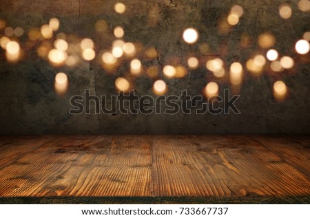 Antique concrete wall with golden bokeh and rustic wooden floor for a christmas decoration