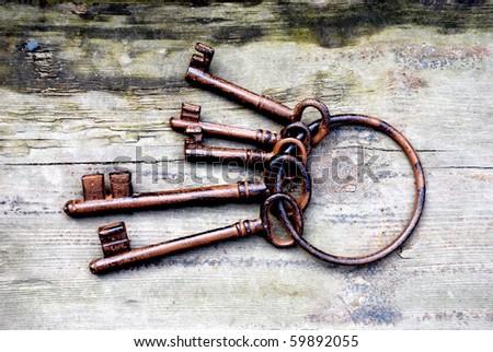 Antique copper keys on old wooden background