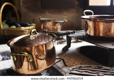 Antique copper pans on 17th century coal stove in preserved kitchen in an old chateau in Burgundy, France.