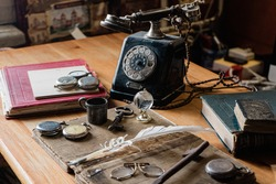 antique desk with accessories: old telephone, books, globe, notes, ink pen, old glasses. and for hours. The picture conveys the atmosphere of antiquity - past years