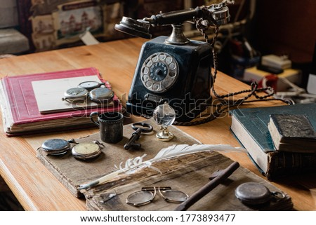 antique desk with accessories: old telephone, books, globe, notes, ink pen, old glasses. and for hours. The picture conveys the atmosphere of antiquity - past years Сток-фото ©