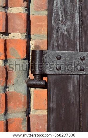 Antique door hinge on wooden door closeup