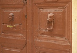 Antique door knocker in the form of a male head stylized as an ancient Egyptian sculpture. A brown wooden bivalve door, poorly painted with cracks, with unusual door knocks, one of which is damaged.