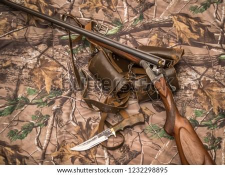 Double-barreled shotgun, bullets, knife and cartridge belt