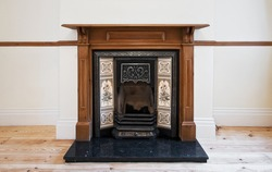 antique fireplace with carved wooden frame and hand painted ceramic tiles