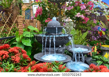Antique fountain at garden. Blue water flowing from stone fountain. Design of antique fountain - Shutterstock ID 1010702263
