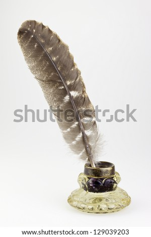 antique glass inkwell and old pen isolated background