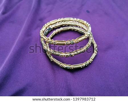 Antique gold  Bangle For Beautiful Hands on violet background #1397983712