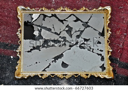 Antique golden picture frame with broken glass on dirty rag background.