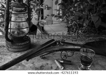 Antique hunting rifle, old hurricann lamp and one glass of wine on a old wooden background. Black and white picture