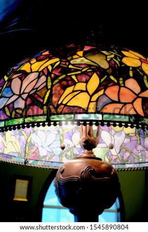 Antique, illuminated, stained glass lampshade in a dark room.