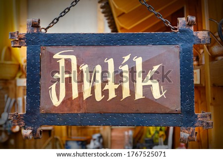 antique in german text on old board in German store. Antik Metal old board in shop. Antik Metal old board in shop. Vintage plate sign hanging with metal chains Stock fotó ©