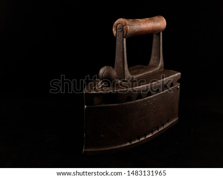 Antique ironing tool, old steel coal iron with a wooden handle. Old iron on a black background.