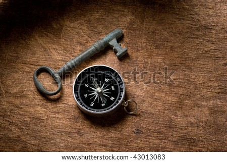antique key and compass on a brown textured background.