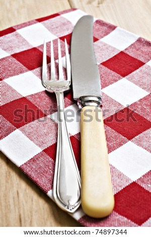 Antique knife and fork on a red and white cloth