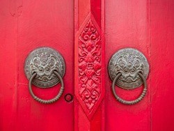 Antique knocker door handles Asian style on the red-painted doors. Lion door handle rings close-up. Wood carving element with floral symmetrical ornament. Door decoration element. Chinese