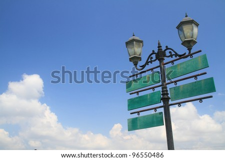 Antique lamp with traffic wood signboard on sky