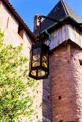 Antique lantern against the background of the fortress wall and tower of the castle Haut-Koenigsbourg (Château du Haut-Kœnigsbourg)