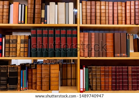 Antique leather cover books on wooden bookshelf in university public library. Reading philosophy or history studying. Education research and self learning concepts
