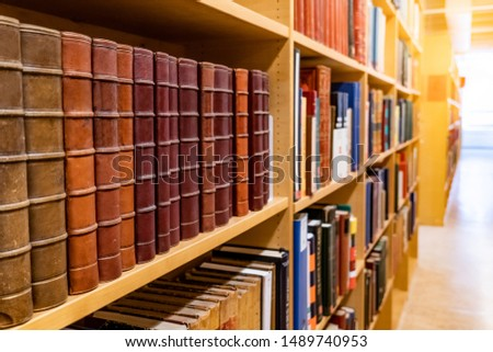 Antique leather cover books on wooden bookshelf with aisle perspective in university public library. Reading philosophy or history studying. Education research and self learning concepts