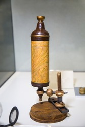 Antique Leeuwenhoek microscope in light brown on a white table, Microbiology scientific instruments.