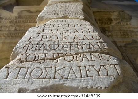 Antique letters on a column. Ephesus. Turkey
