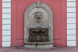 antique lion-shaped drinking fountain embedded in the wall of an old house