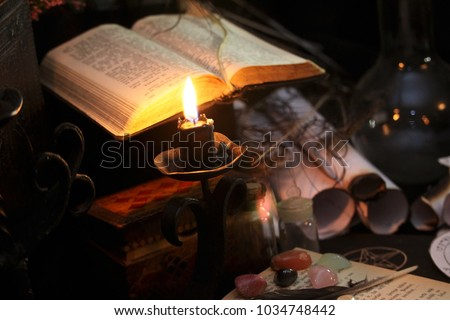 Antique Magic Book. Witchcraft  Peacock feathers and candle background. Black candle Magic Ritual #1034748442
