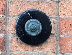 Antique marble and bronze push button door bell in brick wall