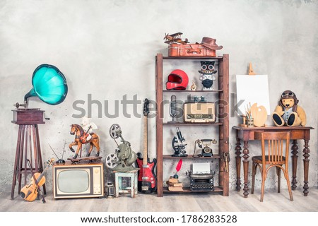 Antique media devices, writers tools, gramophone, film projector, old Teddy Bear toys and white canvas blank on easel, violin and guitar front concrete wall background. Vintage style filtered photo Stockfoto ©