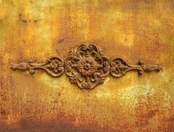 Antique metal ornamental detail on rusty yellow wrought iron wall. Rusty painted old ornate decorative wrought metal grill in dilapidated state. Background and textures.