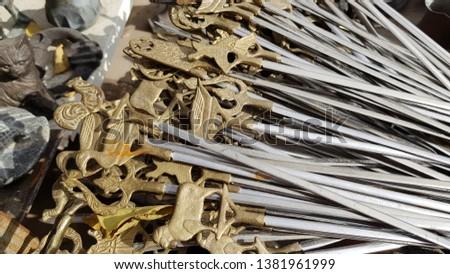 Antique metal skewers with brass sculptural handles and steel blades. Pile of vintage skewers on Turkish bazaar. Yellow metal animal shaped sculptures on handles of barbecue skewers. Retro objects