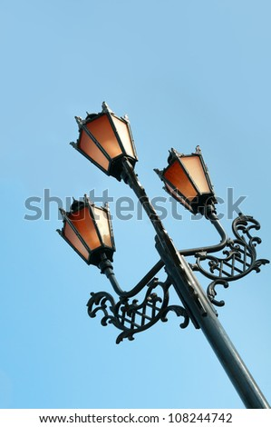 Antique metal street lamp with blue sky on background