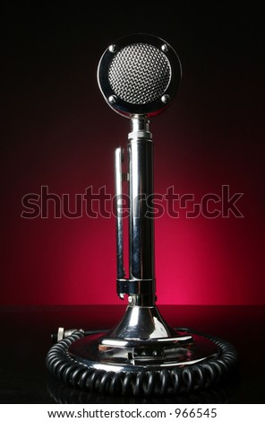 Antique microphone on red background